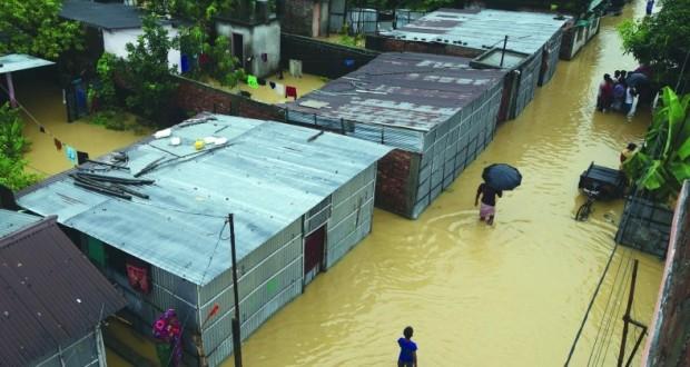 هنود يشقون طريقهم عبر مياه الفيضانات من نهر بانتشاناي في سيليجوري بالهند بسبب هطول الأمطار