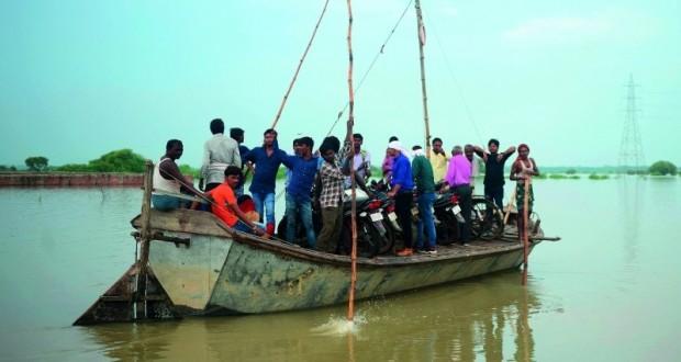 قرويون هنود يعبرون طريقًا مغمورًا بالمياه
